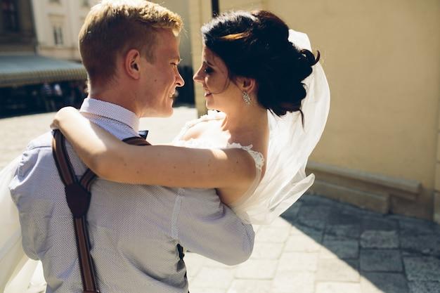 Vista trasera de la novia en los brazos del novio