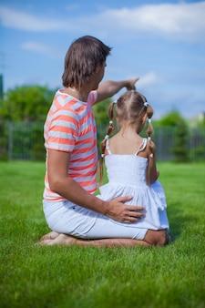 Vista trasera del padre con su hija sentada en el patio al aire libre