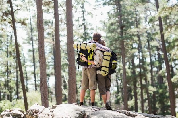 Vista trasera de la pareja abrazándose en roca