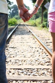 Vista trasera de una pareja amorosa cogidos de la mano y caminando juntos en las vías del ferrocarril para viajar