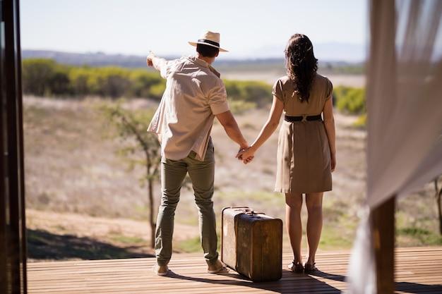 Vista trasera de la pareja apuntando a la vista en un día soleado