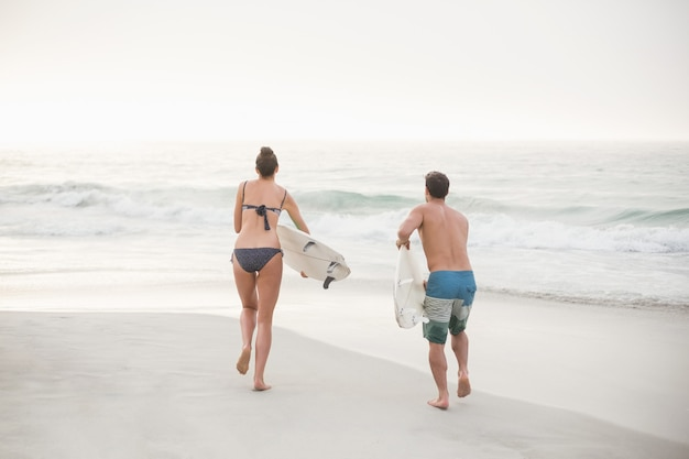 Vista trasera de la pareja corriendo con una tabla de surf en la playa