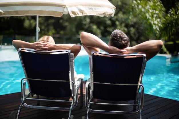 Vista trasera de la pareja descansando en una tumbona