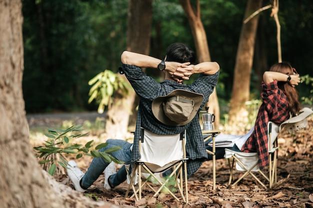 Vista trasera, la pareja de jóvenes adolescentes asiáticos tiene tiempo de relajación con un viaje de campamento, están sentados y con las manos en la parte posterior del cuello en una silla frente a la tienda de campaña con mochila en el bosque