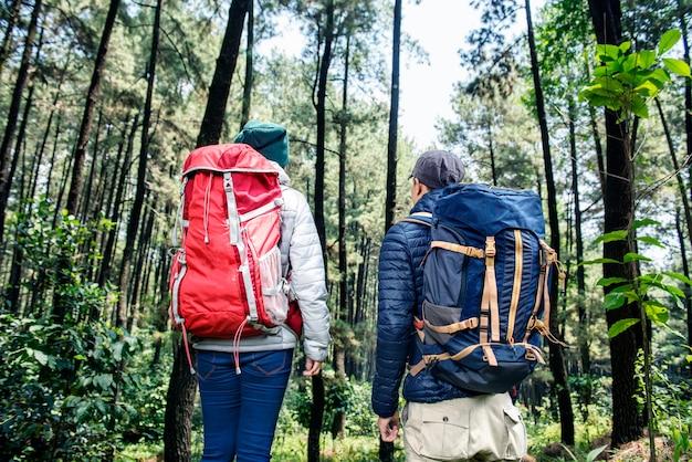 Vista trasera de una pareja de mochileros asiáticos viajando juntos