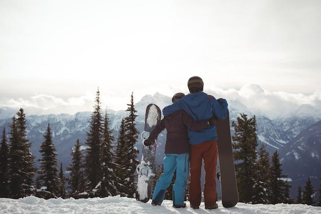 Vista trasera de la pareja sosteniendo snowboard en la montaña durante el invierno contra el cielo