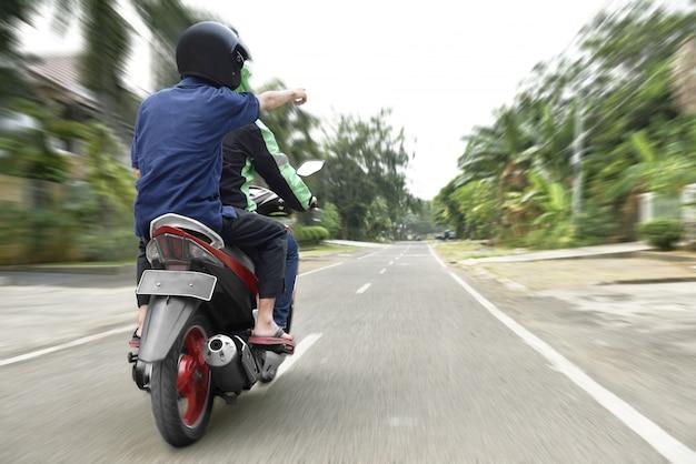 Vista trasera del pasajero dirigiéndose al conductor de taxi en motocicleta.