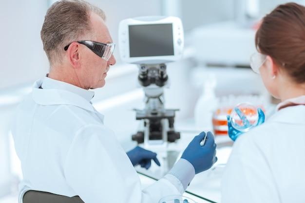 Vista trasera. placa de petri en manos de científicos médicos