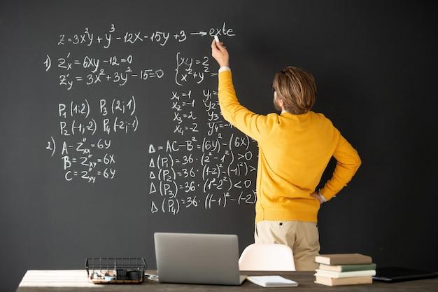 Vista trasera del profesor contemporáneo en ropa informal escribiendo fórmulas en la pizarra y explicándolas a la audiencia en línea en la lección
