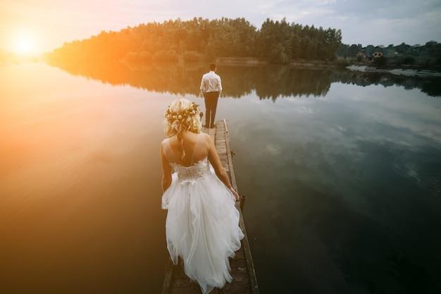 Vista trasera de recién casados en una pasarela de madera al atardecer