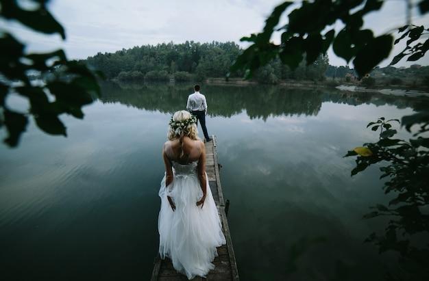 Vista trasera de recién casados en una plataforma de madera