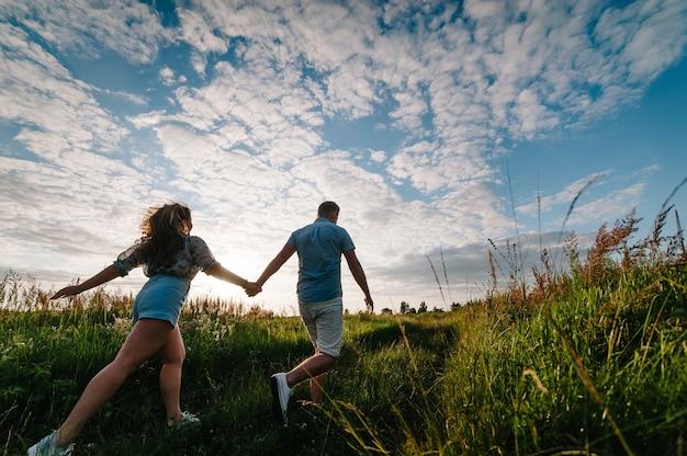 Vista trasera de un romántico hombre y mujer caminando sobre la hierba del campo, la naturaleza disfruta de una impresionante puesta de sol. concepto de familia encantadora cogidos de la mano. pareja joven corriendo y mirando a otro lado.