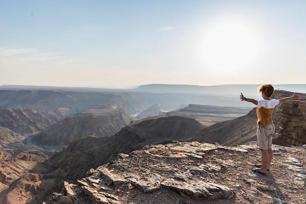 Vista trasera del turista mirando amplia vista sobre el cañón del río fish