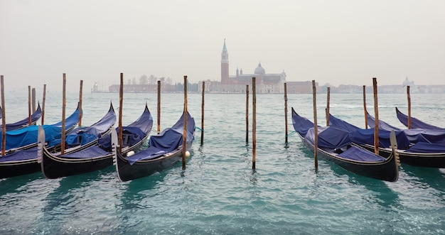 Una vista a través de la laguna en venecia con góndolas en un día brumoso