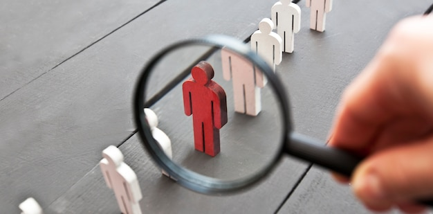 La vista a través de la lupa en una persona roja de madera entre otras personas.