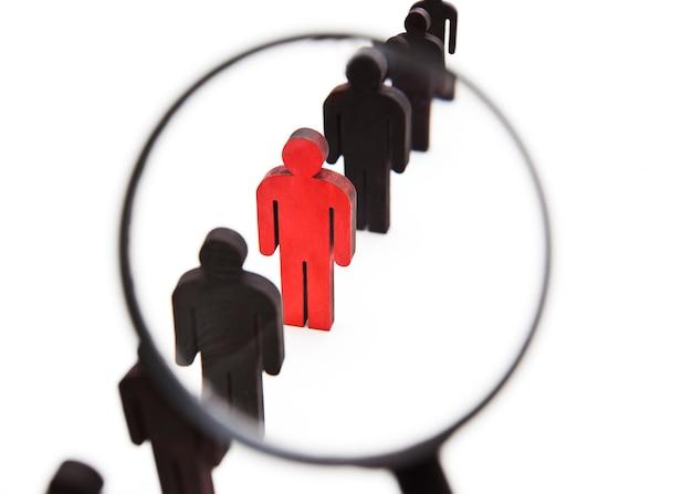 La vista a través de la lupa sobre una persona roja de madera entre otras personas.
