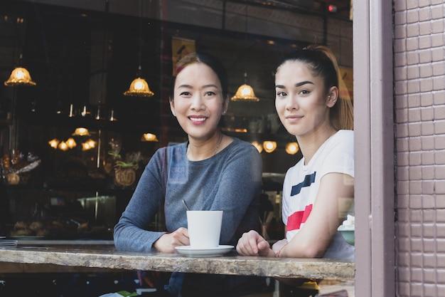 Vista a través de la ventana de mamá e hija sentada en café con taza de café.