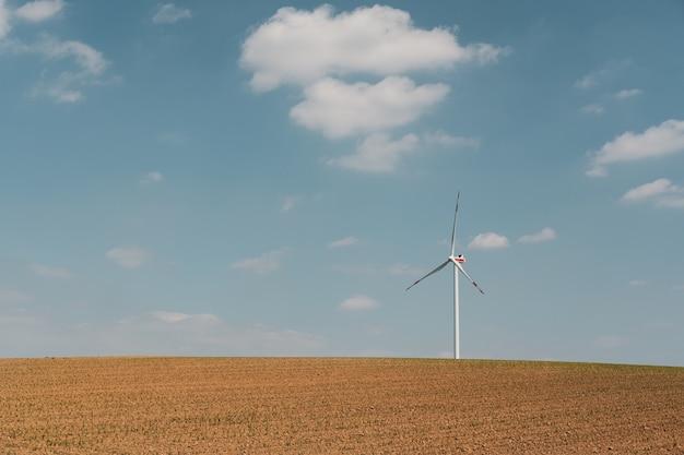 Vista de la turbina eólica y la granja marrón bajo el cielo azul y las nubes blancas