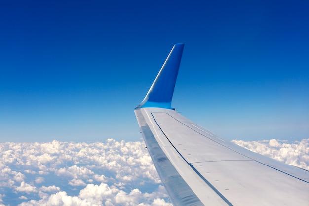 Vista desde la ventana del avión. ala de un avión volando por encima de las nubes blancas.