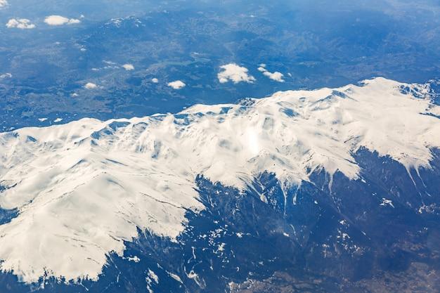 Vista desde la ventana del avión que vuela sobre las montañas.