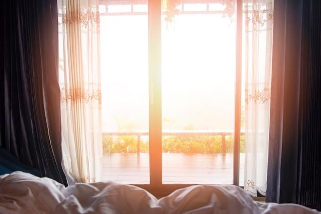 Vista de ventana naturaleza montaña verde en la cama en la habitación mañana y luz solar - ventana de vidrio con cortinas