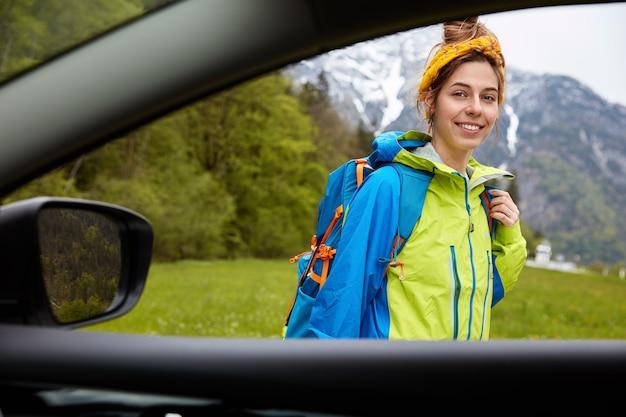 Vista desde la ventanilla del coche de escalador femenino feliz se encuentra al aire libre contra la hermosa vista a la montaña
