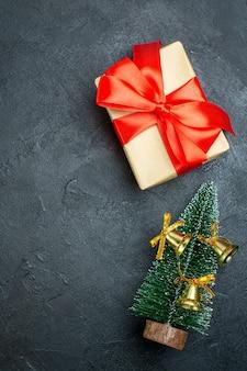 Vista vertical de la caja de regalo con cinta roja en forma de arco y decorado árbol de navidad o fondo negro