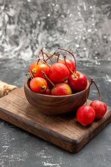 Vista vertical de cerezas rojas en un recipiente marrón y sobre una pequeña tabla de cortar en gris