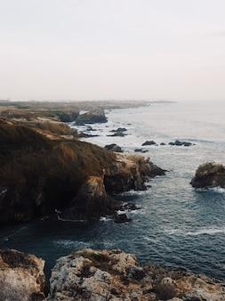 Vista vertical de una costa rocosa con campos de maleza bajo un cielo despejado