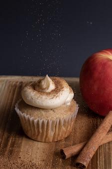 Vista vertical de un cupcake con glaseado mientras espolvorea un café en polvo en la parte superior