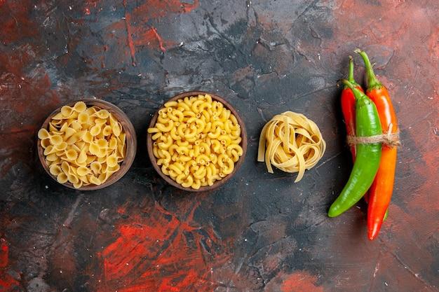 Vista vertical de la deliciosa preparación de la cena con pastas crudas en diversas formas y pimientos atados entre sí sobre fondo de colores mezclados