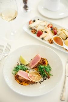 Vista vertical de un delicioso plato de atún con una copa de vino y un set de queso