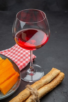 Vista vertical del delicioso vino tinto en una copa de vidrio y queso en rodajas sobre una toalla despojada de rojo sobre un cuadro negro