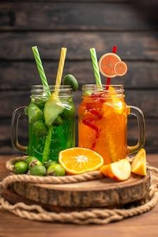 Vista vertical de deliciosos jugos y frutas frescas en una bandeja de madera sobre un fondo marrón