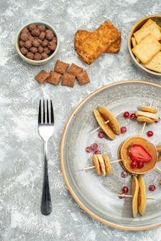 Vista vertical de deliciosos panqueques con chocolate y galletas sobre fondo azul