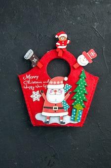 Vista vertical del estado de ánimo navideño con accesorios de decoración y caja de regalo de año nuevo en superficie oscura
