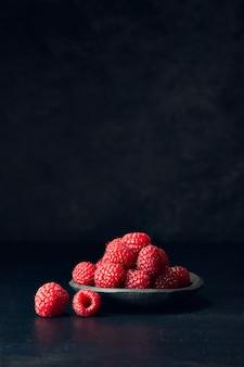 Vista vertical de frambuesas en un plato sobre una superficie negra