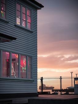 Vista vertical de una hermosa casa de madera con adornos en las ventanas cerca del mar