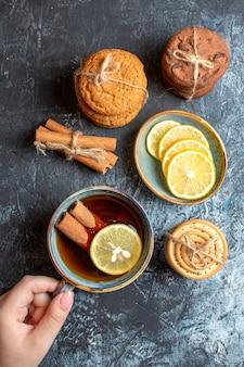 Vista vertical de limones frescos y mano sosteniendo una taza de té negro con galletas de canela apiladas sobre fondo oscuro