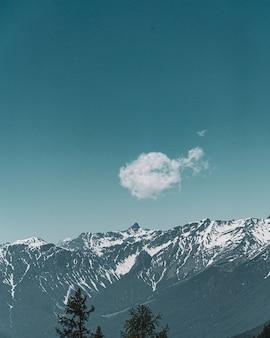 Vista vertical de una linda nube pequeña con el fondo de montañas y cielo azul