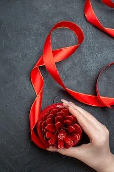 Vista vertical de la mano que sostiene un cono de coníferas con cinta roja sobre fondo oscuro
