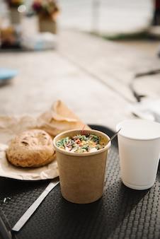 Vista vertical de una mesa con una taza de ensalada de café y pan sobre un fondo borroso