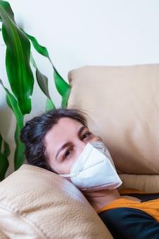 Vista vertical de la mujer infectada con la enfermedad por coronavirus durmiendo en el sofá en casa. quedarse en casa. pandemia mundial de la enfermedad del virus covid 19.
