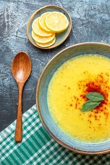 Vista vertical de una olla azul con una sabrosa sopa servida con menta y pimienta junto a una cuchara de madera de limón picado sobre fondo azul.