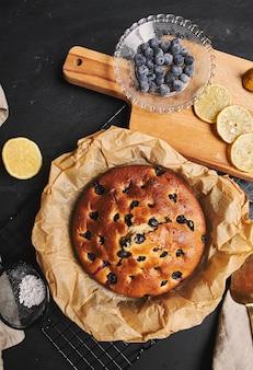 Vista vertical de un pastel de cerezas con azúcar en polvo e ingredientes en el lateral sobre un fondo negro