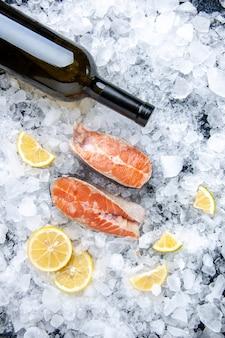 Vista vertical de pescado fresco dividido en dos partes con rodajas de limón y una botella de vino sobre hielos