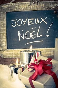 Vista vertical de regalos de navidad con velas encendidas y pizarra.