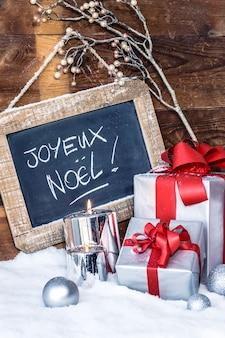 Vista vertical de regalos de navidad con velas y pizarra.
