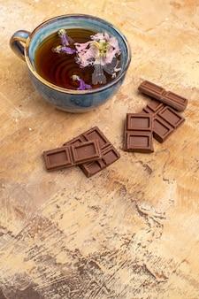 Vista vertical de una taza de té de hierbas caliente y barras de chocolate sobre fondo de colores mezclados