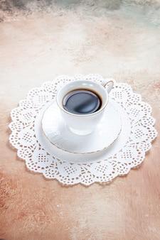 Vista vertical de una taza de té negro sobre una servilleta decorada en blanco en colores